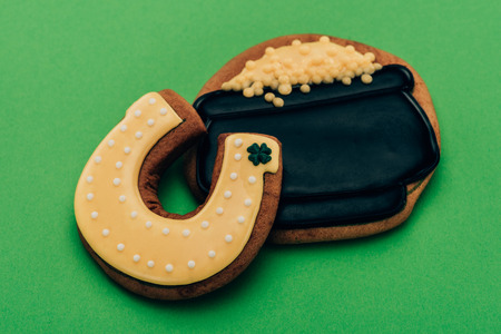 High angle view of icing cookies in shape of horseshoe and pot with coins on green background, St Patricks day concept Stok Fotoğraf