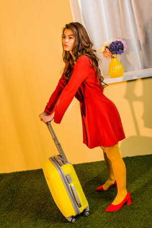 Beautiful retro styled woman in red dress leaning on travel bag at home