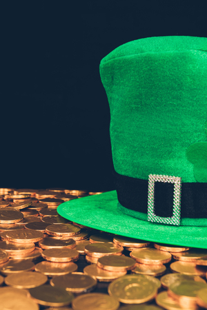 Green hat on shining golden coins isolated on black background, St Patrick's day concept