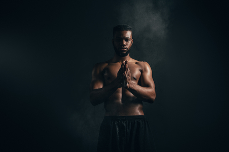 Young African American sportsman applying talcum powder and looking at camera on black background