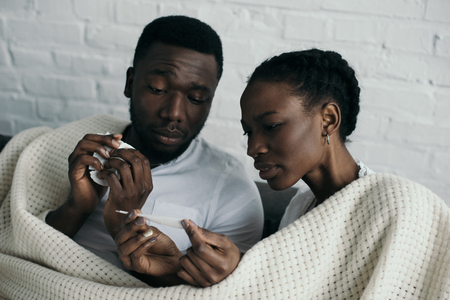 Young African American couple checking thermometer while having flu together at home Banco de Imagens