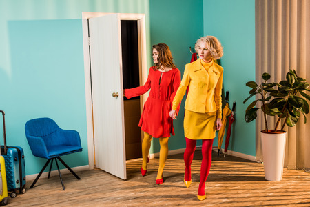 Beautiful retro styled girls in colorful dresses entering apartment and holding hands at home