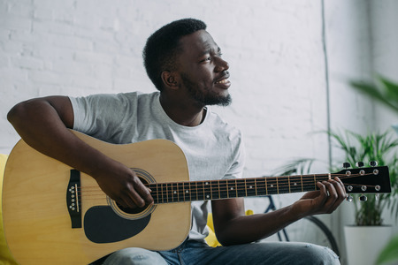 Smiling young African american man playing acoustic guitar and looking away Stock Photo
