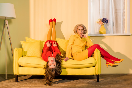 Retro styled beautiful girls in red and yellow dresses on sofa at home Foto de archivo