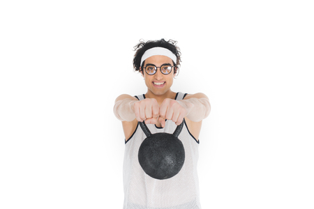 Thin sportsman in eyeglasses holding kettle bell in hands isolated on white background