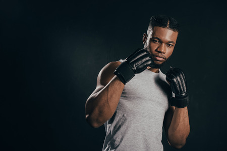 Young African American kickboxer in gloves looking at camera isolated on black background