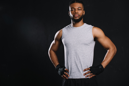 Handsome young African American sportsman standing with hands on waist and looking at camera isolated on black background Stock Photo