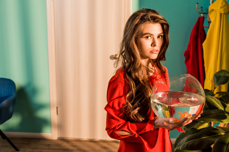 Stylish woman in red dress holding aquarium with gold fish and looking at camera at home