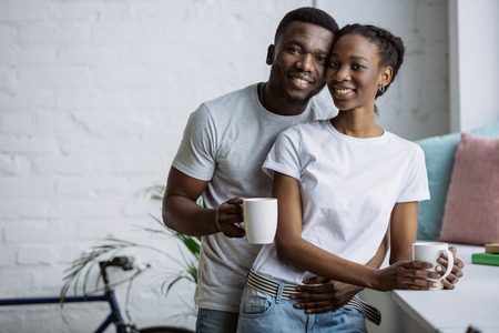 Happy young African American couple holding cups and smiling at camera