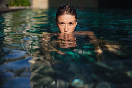 Beautiful young woman immersed in water at swimming pool looking at camera