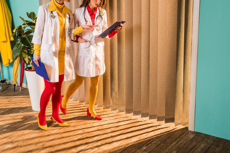 Cropped image of retro styled doctors in colorful tights pointing on clipboard in clinic Stock Photo