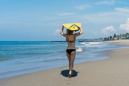 Rear view of female surfer holding surfboard on head and walking on beach at the sea