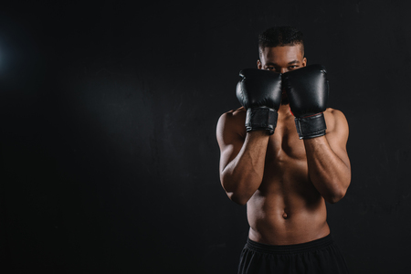 Young shirtless African American boxer in boxing gloves looking at camera isolated on black background
