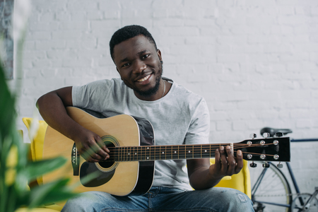 Young African American man playing guitar and smiling at camera Stock Photo