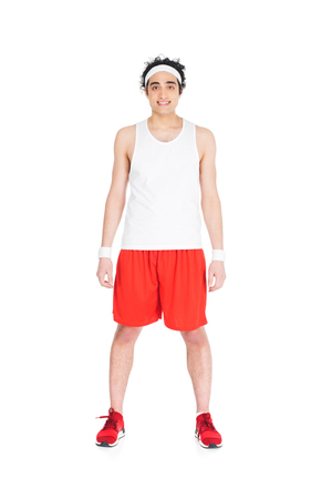 Young skinny man in jogging shoes and shorts standing isolated on white background