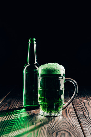 Glass and bottle of green beer on wooden tabletop, St Patricks day concept