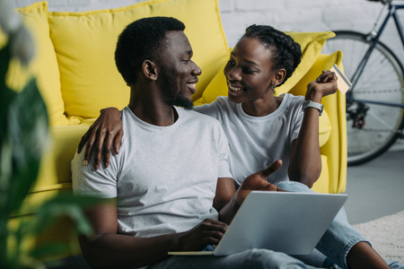 Happy young African American couple with laptop and credit card smiling each other at home