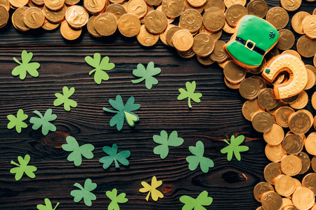 Top view of paper shamrock and golden coins on wooden table, St Patrick's day concept Stock Photo