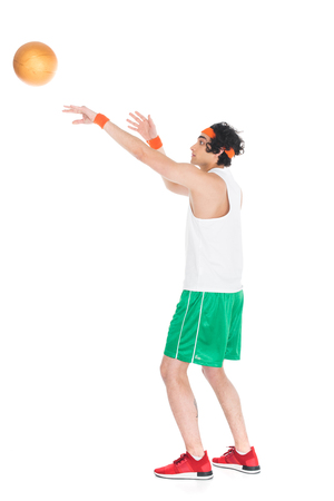 Side view of thin young basketball player throwing ball isolated on white background