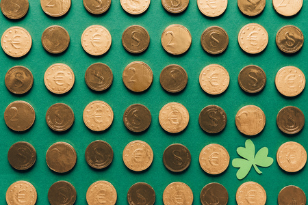 Top view of pattern of golden coins and shamrock on green background, St Patricks day concept