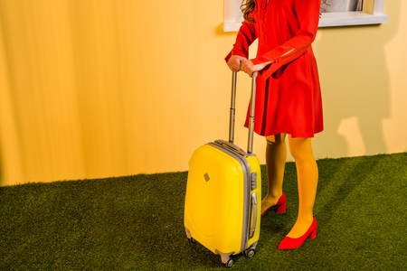 Cropped image of retro styled woman in red dress standing with travel bag at home