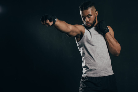Serious young African American kickboxer exercising isolated on black background