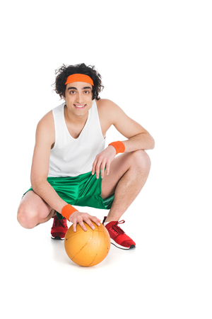 Smiling skinny basketball player sitting with ball isolated on white background 写真素材