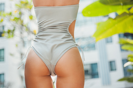 Cropped shot of woman in grey swimsuit with fit buttocks Banque d'images