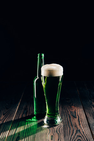 Shining glass and bottle of green beer on wooden table, St Patricks day concept Stok Fotoğraf