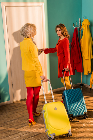 Beautiful old-fashioned girls in colorful dresses with travel bags walking to door at home Stock Photo