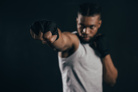 Close-up view of young African American kickboxer training on black background