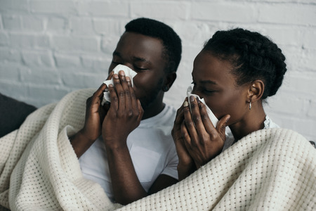 Young diseased couple holding paper napkins and lying under blanket together at home Stockfoto