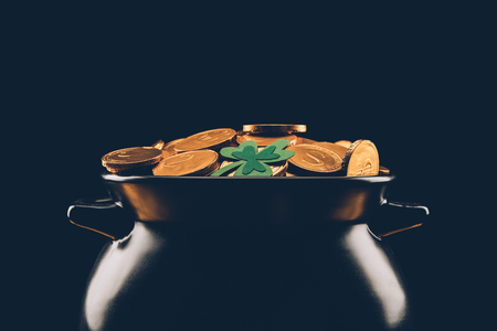 Black pot with golden coins isolated on black background, St Patrick's day concept Stock Photo