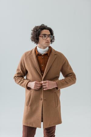 Stylish young man in eyeglasses buttoning coat isolated on grey background Stock Photo