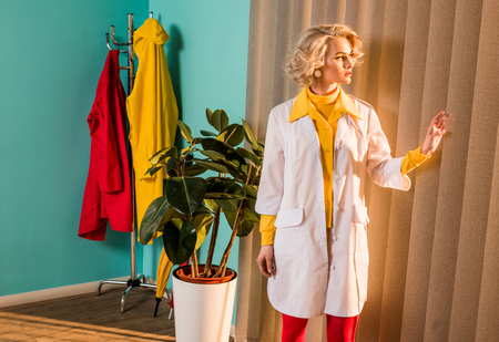 Beautiful retro styled doctor in colorful dress and white coat looking through jalousie in clinic