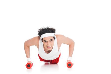 Skinny sportsman doing push ups with dumbbells isolated on white background Stock Photo