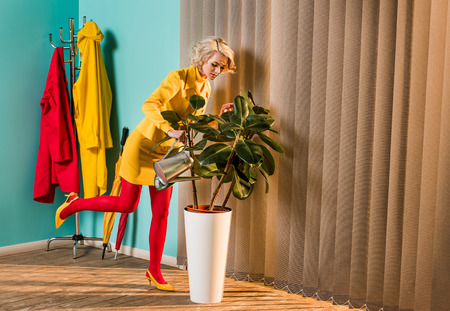 Stylish attractive woman in colorful dress watering plant with watering can at home