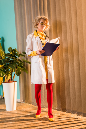 Beautiful retro styled doctor in colorful dress reading diagnosis in clipboard in clinic Stock Photo