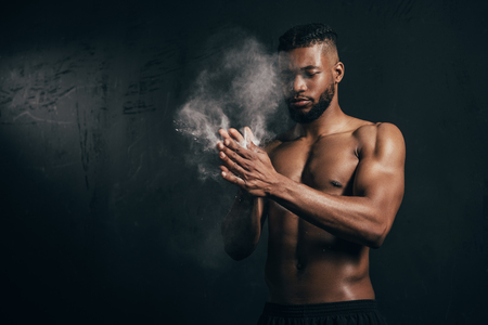 Young bare-chested African American sportsman applying talcum powder on hands on black background