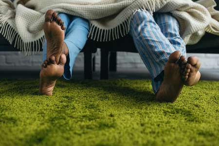 Cropped shot of barefoot African American couple in pajamas spending time together at home