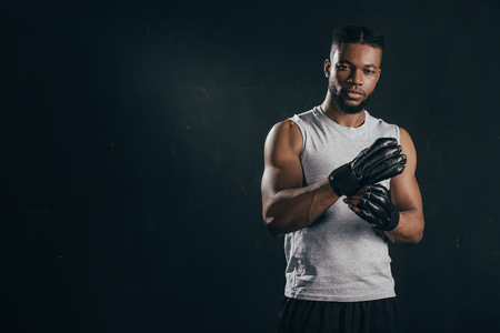 Young African american kickboxer wearing gloves and looking at camera isolated on black background Stock Photo