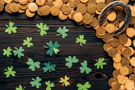 Top view of shamrock, golden coins and horseshoe on wooden table, St Patricks day concept