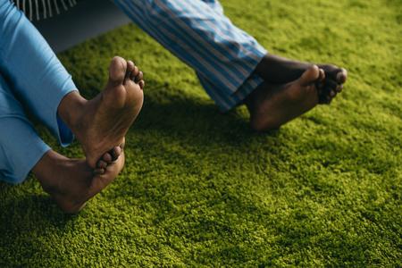 Nahaufnahme Teilansicht eines barfüßigen afroamerikanischen Paares im Pyjama, das Zeit zusammen zu Hause verbringt