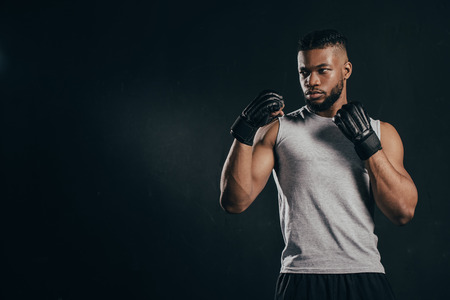 Serious muscular young African American sportsman in gloves training isolated on black background