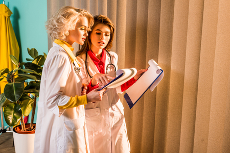 Beautiful stylish doctors in white coats looking at clipboard in clinic Stock Photo