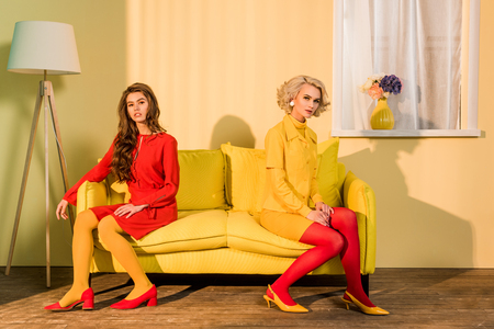 Retro styled beautiful girls in colorful dresses sitting on sofa and looking at camera at home Stock Photo