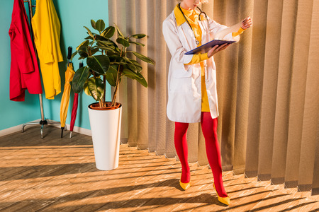 Cropped image of retro styled doctor in colorful dress and tights looking at clipboard in clinic