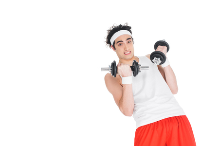 Young skinny man in headband exercising with dumbbells isolated on white background