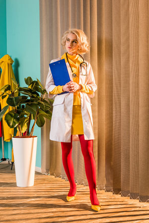 Beautiful retro styled doctor in colorful dress holding clipboard and looking away in clinic Stock Photo