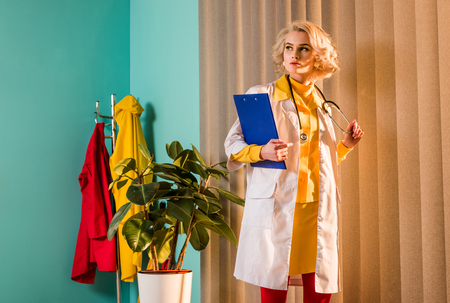 Beautiful retro styled doctor in colorful dress holding clipboard and stethoscope in clinic Stock Photo